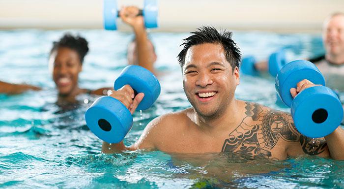 Kille tränar med hantlar i simbassäng